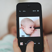 A two month old baby girl is photographed on an iPhone  while breast feeding in bed with her mother. Photo Tim Clayton