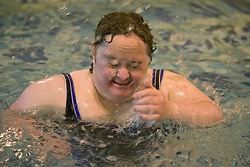 Day Service user with learning disability splashing about in the water at a local swimming pool,