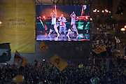 """Kiev, Ukraine, 21/05/2005..The fiftieth Eurovision Song Contest..The crowd of some 300,000 packed into Maidan Square wave revolutionary flags while watching Ukrainian contestants Green Jolly perform their anthem """"Together We Are Many""""."""