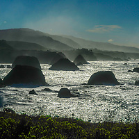 Pacific Ocean waves crash ashore between islands near Elk, California.