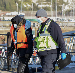 DATE CORRECTION © Licensed to London News Pictures. 13/04/2021. Dover, UK. A migrant is helped ashore by a Border Force officer at Dover Harbour in Kent after crossing the English Channel. Home Secretary Priti Patel has pledged an overhaul of asylum seeker rules, with refugees having their claim assessed based on how they arrive in the UK. Photo credit: Stuart Brock/LNP