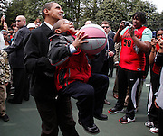 U.S. President Barack Obama picks up a little boy to shoot a basketball as part of the Annual Easter Egg Roll on the South Lawn at the White House in Washington, April 13, 2009.    REUTERS/Jim Young
