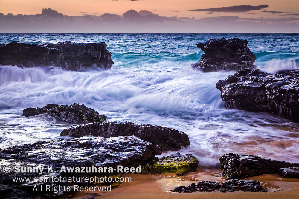 Wave crashing through rocks at dawn, Sandy Beach, Oahu Island, Hawaii.
