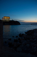A boat sails out of the harbor at dusk in Marseille, France. On the hill is the Palais du Pharo.