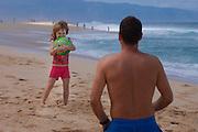 A little girl joyfully holds a beach ball her father has trrown on the beach in Hawaii