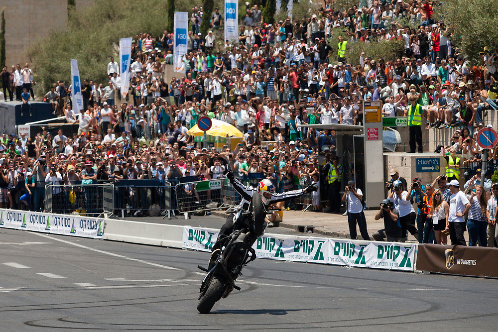 Stunt rider Chris Pfeiffer performs a trick on his BMW motorcycle during the second day of the Jerusalem Formula Peace Road Show, in Jerusalem, Israel, on June 14, 2013. The first-ever two-day Jerusalem Formula Peace Road Show includes Formula One racing teams, Scuderia Ferrari and Marussia, Ferrari Challenge cars, drifting cars and Grand Prix motorcycles all participating in the show, whose circuit passes landmarks such as Jerusalem's Old City walls.