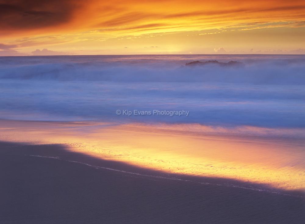 Waves crash along a sandy beach - Big Sur, California.
