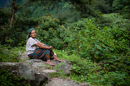A portrait of a sherpa woman taking a rest as her goats graze, Annapurna Sanctuary, Nepal