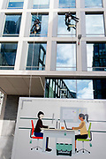 Above an illustration of two women office workers at their desks who appear on the side of parked van, two male contractors abseil down to clean the windows of corporate offices in the City of London, the capital's financial district, on 26th October 2020, in London, England.