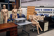 From the side of a road in south London, we see a group of naked female mannequins, standing and sitting with furniture on the forecourt of an office supplies business. A clearance sign stands partly-obscured but one's attention is to the physiques of each model that tends to signify whichever the fashion industry has decreed is the 'look' of the decade – whether buxom or skinny – and shop windows are therefore occupied with the clothing shapes of the day. Some women stand in that classic fashion pose, with arms at the side and one leg in front of the other, or sitting with one leg elegantly crossed: All designed to make the clothes they wear look attractive.