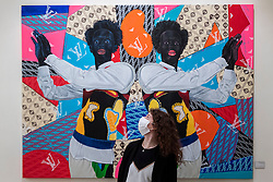 """© Licensed to London News Pictures. 14/10/2021. LONDON, UK. A staff member views """"Things fall apart"""", 2021, by Anjel (Boris Anje). Preview of 1-54 Contemporary African Art Fair, the leading international art fair dedicated to contemporary art from Africa and its diaspora.  Works by around 48 exhibitors are on show in a show which runs 14 to 17 October at Somerset House.  Photo credit: Stephen Chung/LNP"""