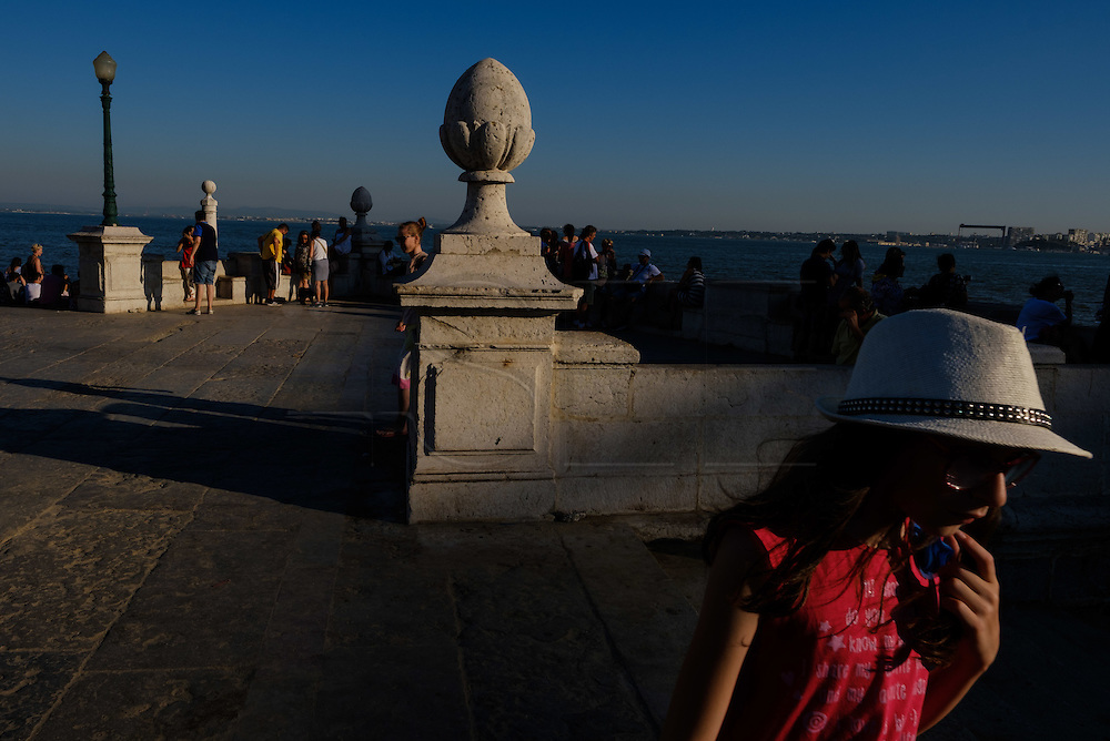 A girl walks at Cais das Colunas (Columns Pier) by the Tagus riverside. The pier is part of Terreiro do Paço, the largest Lisbon square, and is one of the most well-know place to visit in Lisbon.