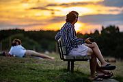 People enjoy a fresh evening as they observe the sunset after a hot day in the Hampstead Heath Park in Northwest London on Friday, Aug 7, 2020, as the UK could see record-breaking temperatures with forecasters predicting Friday as the hottest day of the year. Exceptionally hot weather is set to continue in parts of the UK throughout the weekend, the Met Office said. The highest temperatures are expected in England and Wales, with a fresher weather forecast for Scotland and NI. (VXP Photo/ Vudi Xhymshiti)
