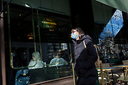 On the day that the UK Government's Chief Scientific Advisor, Sir Patrick Vallance said that the Coronavirus Covid-19 outbreak was now spreading person to person in the UK, a foreign student wears a surgical mask while walking along Aldwych during his lunch-hour, from nearby London School of Economics (LSE), on 6th March 2020, in London, England.