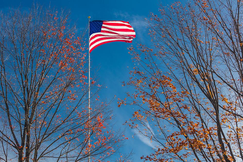 Windblown American flag, afternoon light, October, Hillsborough County, Hancock, New Hamphshire, USA