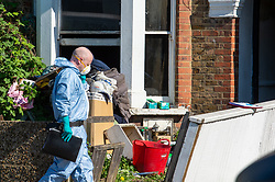 © Licensed to London News Pictures. 25/04/2020. London, UK. A forensic investigator enters a property at the scene of a fatal house fire. A man has died in a house fire in Earlsfield, Wandsworth. Firefighters found the man in a ground floor bedroom. He was brought out of the property by fire crews but he died at the scene. London Fire Brigade was called at 07:36 BST and the fire was under control by 08:33 BST. Photo credit: Peter Manning/LNP
