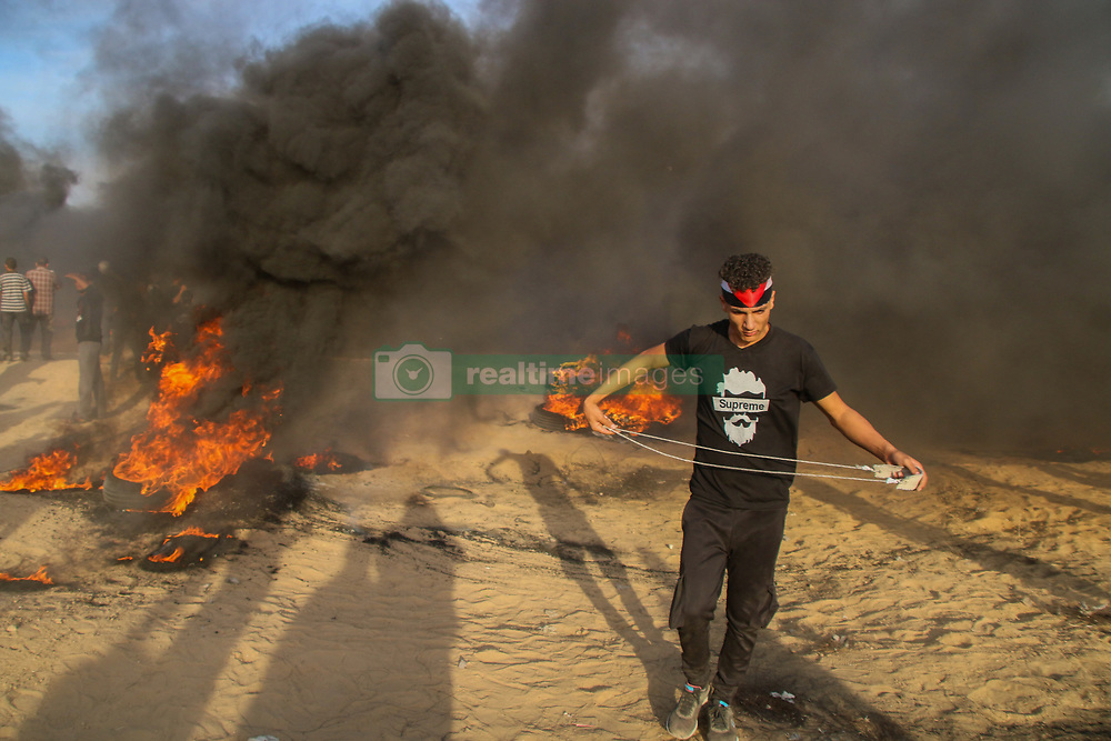 October 5, 2018 - Palestinian protesters clash with the Israeli Security Forces on the east of khan Yunis in the southern Gaza Strip on October 5th, 2018. According to Gaza Health Ministry three Palestinian protesters, including a 12-years-old boy, were killed by live Israeli fire, while 124 were injured by tear gas and live ammunition used against them by the Israeli Security Forces during the clashes. Protests took place in several locations along the Gaza-Israeli border fence with some of the Palestinian protestors burning tires and hurling rocks at IDF soldiers behind the fence. According to the Israeli army some demonstrators threw make-shift explosive devices towards the fence. The Gaza health ministry has identified two of the protesters killed as 12-year-old Faras Hafez Assarsawei and 24-year-old Mahmud Abu Sama'an.  Since March 30, Palestinians have been holding weekly demonstrations calling for the lift of the 11-year-long Israeli blockade on the Palestinian enclave, the right of Palestinian refugees to return to their ancestral homes, and in protest at the recent decisions by the US administration regarding the Jerusalem status and to cut their funding to UNRWA, the UN relief agency for Palestinian refugees. At least 193 Palestinians have been killed and over 21,000 have been injured since the protests started on 30th March (Credit Image: © Ahmad Hasaballah/IMAGESLIVE via ZUMA Wire)