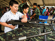 10 JANUARY 2015 - BANGKOK, THAILAND:  A Thai child handles a machine gun during Children's Day celebrations at a Royal Thai Army base in Bangkok. National Children's Day falls on the second Saturday of the year. Thai government agencies sponsor child friendly events and the military usually opens army bases to children, who come to play on tanks and artillery pieces. This year Thai Prime Minister General Prayuth Chan-ocha, hosted several events at Government House, the Prime Minister's office.   PHOTO BY JACK KURTZ