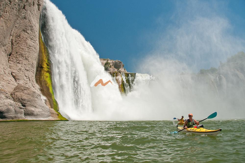 Two men smiling while kayaking Shoshone Falls on the Snake River in Twin Falls, Idaho.