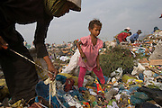 RUBBISH DUMP RECYCLING. South East Asia, Cambodia, Phnom Penh. Smokey Mountain, Steung Mean Chey, is Phnom Penh's municipal rubbish dump. Thousands work there, some 600 minors and 2000 adults, recycling the city's rubbish, dumped there by garbage trucks every day. The dump is notorious as many very young children work there. People eat and sleep overnight in the rubbish and fumes, under plastic tarpaulins or in the open air. They work 24 hours a day, like miners, with headlamps at night, collecting plastic, metals, wood, cloth & paper, which they sort and clean, weigh and sell, to be carried away for recycling. A day's work typically brings less than a dollar per person. One and a half to two dollars per day per family. The overpowering, acrid odour of grey smokey fumes blows across the dump, from which the place gets its name 'Smokey Mountain'. It can be smelt miles away. The shantytowns and squats, the recycling worker's homes butt onto or are inside the dump itself. There is no running water, sanitation and many are ill. Children often work with friends or relatives. Religious and ngo's help some children, but this is often resisted by families who need the extra income they generate./// Jakoy and Yan, sisters aged 10 and 7 years old. They work 6-8 hours per day, sometimes earning as much as 50 cents. They enjoy being with their family but  not the work.