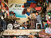 "06 NOVEMBER 2015 - YANGON, MYANMAR: Workers in a luggage repair shop in Yangon. Some economists think Myanmar's informal economy is larger than the formal economy. Many people are self employed in cash only businesses like street food, occasional labor and day work, selling betel, or working out of portable street stalls, doing things like luggage repair. Despite reforms in Myanmar and the expansion of the economy, most people live on the informal economy. During a press conference this week, Burmese opposition leader Aung San Suu Kyi said, ""a great majority of our people remain as poor as ever.""  PHOTO BY JACK KURTZ"
