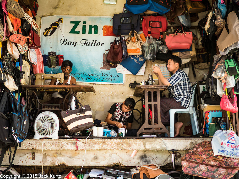 """06 NOVEMBER 2015 - YANGON, MYANMAR: Workers in a luggage repair shop in Yangon. Some economists think Myanmar's informal economy is larger than the formal economy. Many people are self employed in cash only businesses like street food, occasional labor and day work, selling betel, or working out of portable street stalls, doing things like luggage repair. Despite reforms in Myanmar and the expansion of the economy, most people live on the informal economy. During a press conference this week, Burmese opposition leader Aung San Suu Kyi said, """"a great majority of our people remain as poor as ever.""""  PHOTO BY JACK KURTZ"""