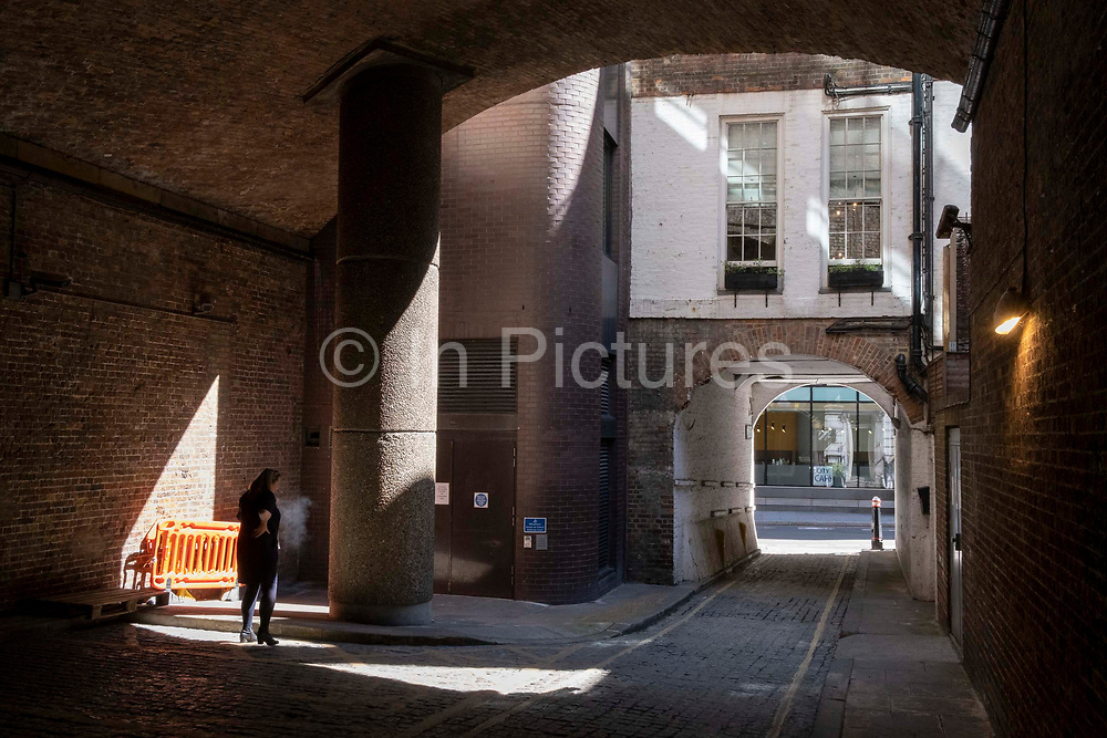 A woman stands in a small amount of sunlight to smoke a quiet cigarette in an underpass beneath the platforms of Fenchurch Street station in the City of London, the capitals financial district, on 8th June 2021, in London, England.