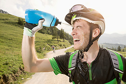 Mountain biker pouring water on his face, Kampenwand, Bavaria, Germany