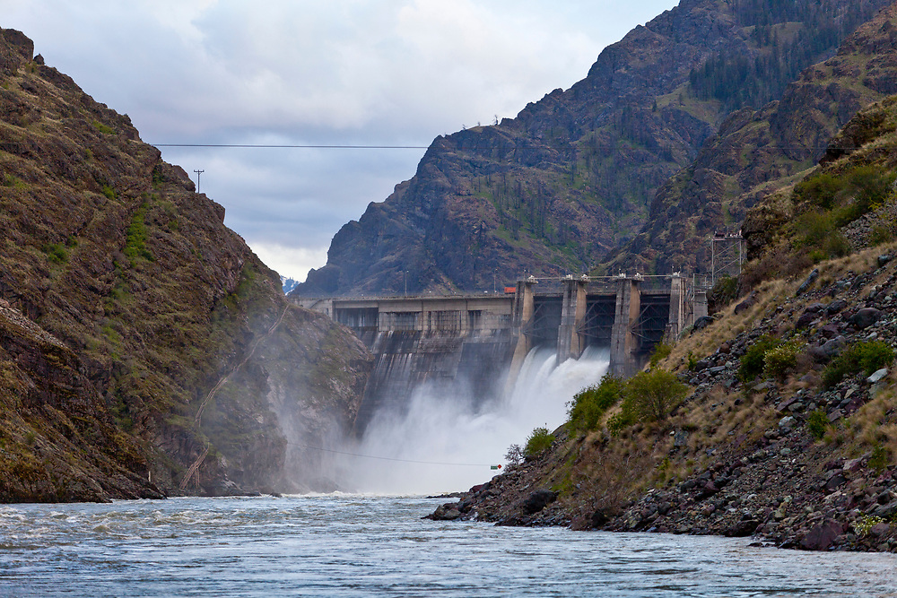 Hells Canyon Dam Spillway releases huge volumes of water back into the Snake River with Idaho on the left and Oregon on the Right.  Licensing and Open Edition Prints.