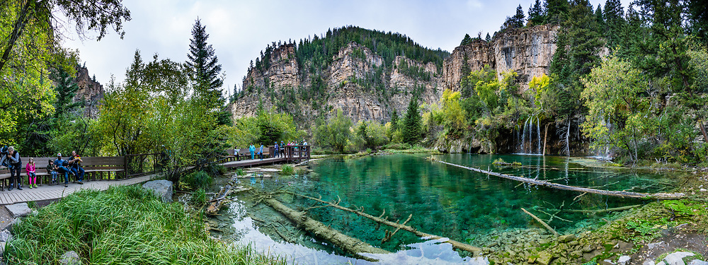 Hanging Lake, along East Fork Dead Horse Creek in Glenwood Canyon, White River National Forest, Colorado, USA. From the trailhead 7 miles east of Glenwood Springs along Interstate 70, follow the Glenwood Canyon Bike and Pedestrian Path east then ascend Dead Horse Creek (a tributary of the Colorado River), for 4 miles round trip gaining 1200 feet, including the nice side trip to Spouting Rock falls. Dissolved carbonate minerals color its water turquoise. The fragile shoreline is travertine, created when dissolved limestone from the Mississippian Period Leadville Formation is deposited in layers on rocks and logs. The shallow bed of Hanging Lake formed on a fault line where the valley floor above sheared and dropped. This image was stitched from multiple overlapping photos. This image was stitched from multiple overlapping photos.