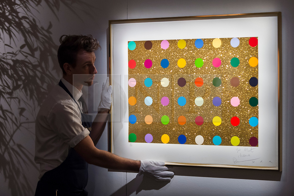 """© Licensed to London News Pictures. 25/10/2019. LONDON, UK. A technician presents """"Untitled (Gold gift spot)"""", 2008, by Damien Hirst (Est. GBP5-7k). Preview of """"GOLD: The Midas Touch"""" at Sotheby's in New Bond Street.  Artworks spanning six centuries dedicated to gold will be offered for sale on 29 October.  Photo credit: Stephen Chung/LNP"""