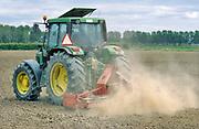 Nederland, Bergharen, 15-5-2020  Een landbouwer egaliseert zijn akker voorafgaand aan het zaaien, poten . Door de aanhoudende droogte die nu in april al erger is als ooit tevoren , waait er veel stof op rond de trekker . Foto: Flip Franssen