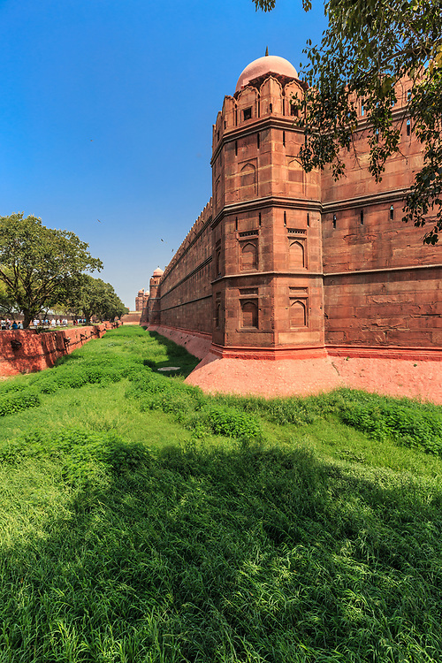 The huge wall and moat in Red Fort in Delhi, India. The Red Fort was the residence of the Mughal emperor for nearly 200 years, until 1857. One of the attractions of Red Fort is the great and huge two kilometer long wall.