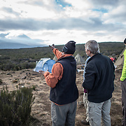 A guide points out the way for that day's hike from Shira 1 Camp towards the mountain peak in the distance on Mt Kilimanjaro.