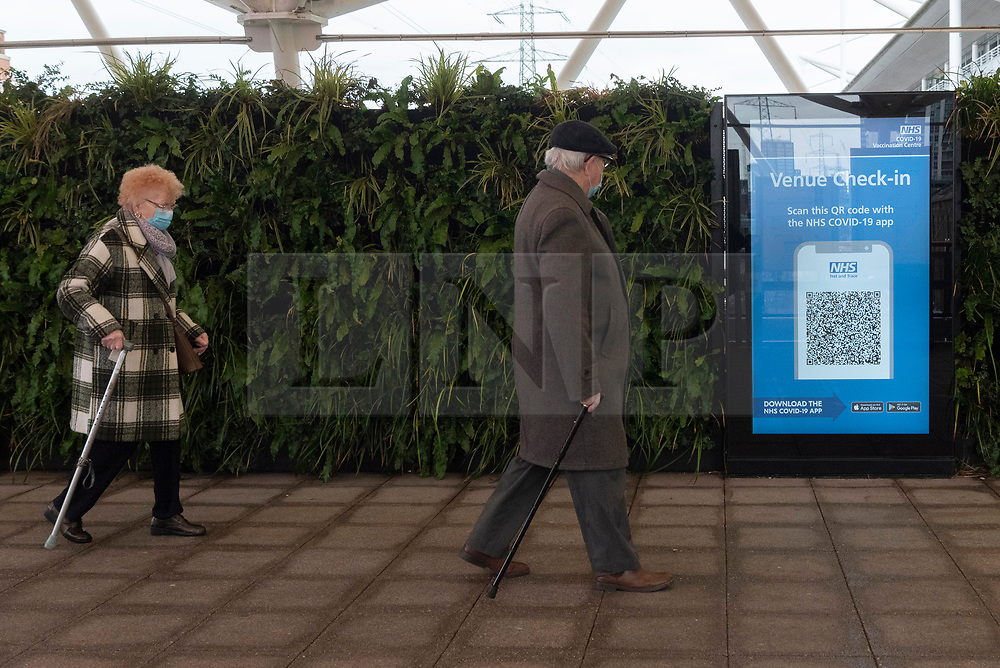 © Licensed to London News Pictures. 11/01/2021. London, UK. An elderly man and woman walk to the Excel Centre Nightingale Hospital to receive a Covid-19 vaccination jab. The hub is one of a few hubs around the Uk to administer mass vaccination jabs. Photo credit: Ray Tang/LNP