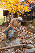 Robert Runyon uses hand tools to shape rock outside of his home in Sugar Tree Hollow in Winslow, Arkansas, for Out Here Magazine. Photo by Beth Hall