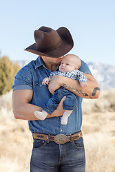 muscular cowboy holding a baby outdoors
