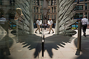 Londoners walk past the sculpture entitled City Wing on Threadneedle Street in the City of London, the capitals financial district, on 24th July 2018, in London, England. City Wing is by the artist Christopher Le Brun. The ten-metre-tall bronze sculpture is by President of the Royal Academy of Arts, Christopher Le Brun, commissioned by Hammerson in 2009. It is called 'The City Wing' and has been cast by Morris Singer Art Founders, reputedly the oldest fine art foundry in the world.