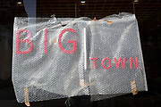 A detail red lettering, the frontage of a new restaurant business to be called Big Town and offering West African food, is still covered in Bubble-Wrap during the propertys conversion on the Walworth Road in south London, on 23rd August 2019, in London, England.