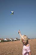 Young blonde girl child flying a kite on shingle beach, Shingle Street, Suffolk, England, UK