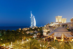 View of resort hotels in evening at Madinat Jumeirah and Burj al Arab hotel to rear in Dubai in United Arab Emirates