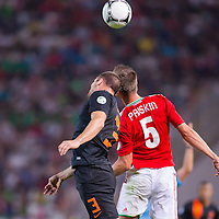 Netherlands' Ron Vlaarhun (L) and Hungary's Tamas Priskin (R) fight for the ball during aWorld Cup 2014 qualifying soccer match Hungary playing against Netherlands in Budapest, Hungary on September 11, 2012. ATTILA VOLGYI
