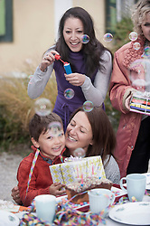Mother hugging her son on his birthday party and smiling, Bavaria, Germany