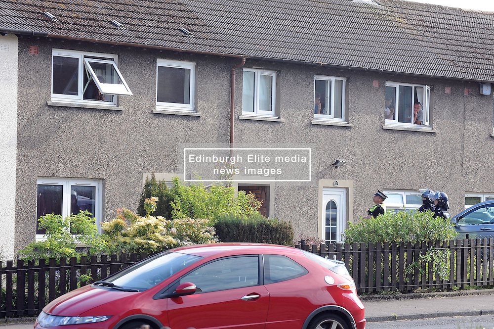 Police Scotland officers in riot gear and units from the local fire station attended a seige in a house in Lomond Crescent Dunfermline while neighbours look on from their windows<br /> <br /> (c) David Wardle | Edinburgh Elite media