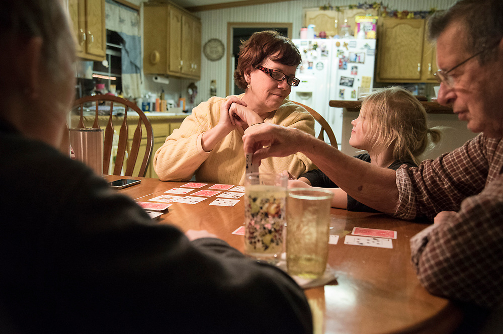 Teresa Trout  (center) plays cards with two granddaughters and her father, Jim Dillie, at her home in Amesville. That night her son-in-law and granddaughters had stopped by to pass time until the high water blocking Highway 550 became passible. Born and raised in the village, Teresa can recall several of the town's most memorable floods.