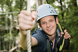 smiling teenager in a climbing crag, close-up