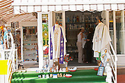A shop with souvenirs for pilgrims, with things for sale. Madonna statue, rosary beads, post cards, umbrellas robes looking like priest's clothing. Medugorje pilgrimage village, near Mostar. Medjugorje. Federation Bosne i Hercegovine. Bosnia Herzegovina, Europe.