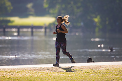 A woman runs past the boating lake as a beautiful morning greets Londoners in Regents Park. London, May 09 2018.