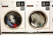 Two commercial tumble drier machines drying clothes in a launderette Wadebridge, Cornwall, UK.  The energy for the launderette is sourced from roof solar panels and is part of a scheme to make this town the first to be powered by renewable sources in the UK.