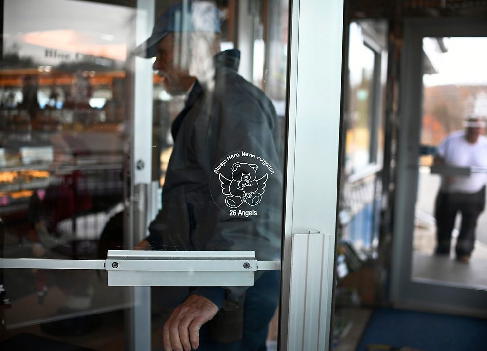 """On the door of the Blue Colony Dinner, a frayed sticker of a teddy bear with wings cradling a smaller bear, with a message declaring Newtown's """"26 Angels"""" are """"Always Here, Never Forgotten., seen here, Saturday, Dec. 2, 2017, in Newtown, Conn.  (Jessica Hill for the New York Times)"""